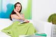 junge frau sitzt mit touchbook auf dem sofa
