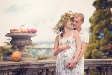 A couple in love during pregnancy in the park with fruit and mel