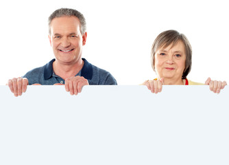 Old age couple holding blank banner ad