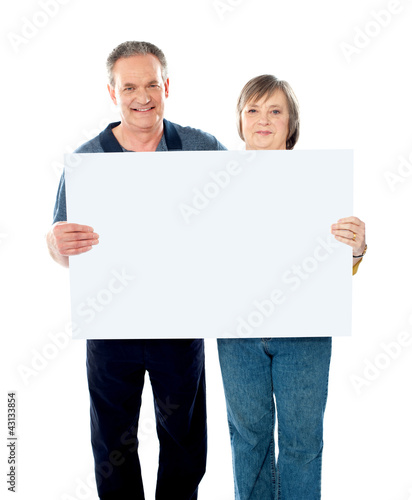 Husband and wife displaying advertising board