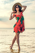 girl in a summer dress and straw hat dancing on the beach