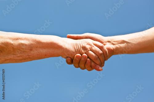 Handschlag einer alten Frau und einem jungen Mann vor blauem Him