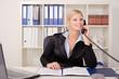 Blonde junge Frau telefoniert am Schreibtisch