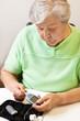 Seniorin schiebt Teststreifen in das Blutzuckermessgerät