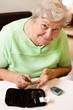 Eigenständige sorglose Seniorin beim Blutzucker messen