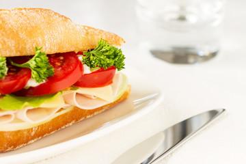 Sandwich with ham, cheese, arugula and tomato