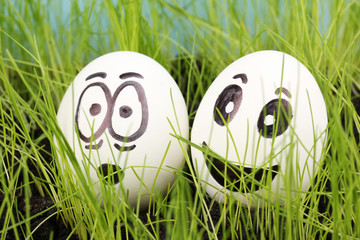 White eggs with funny faces in green grass