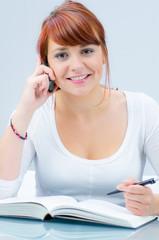 freundliche junge frau telefoniert beim lernen