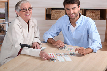 Young playing cards with senior woman