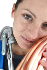 Woman holding copper pipe and bending tool