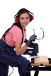 Young woman using miter saw