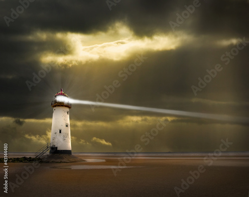 lighthouse in a storm with beam shining to sea