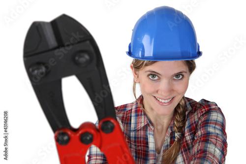 female plumber holding giant spanner