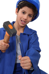 A kid dressed as a construction worker with a hammer.
