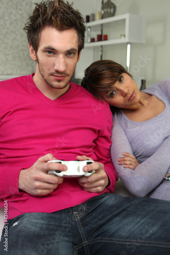 Woman watching boyfriend play video-games
