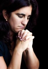 Depressed hispanic woman praying isolated on black