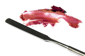 red lipstick smeared on white background with metallic spatula