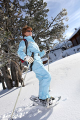 Mature woman having a walk in snowshoes