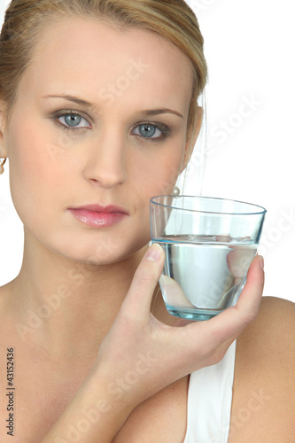 Serious woman with glass of water in hand