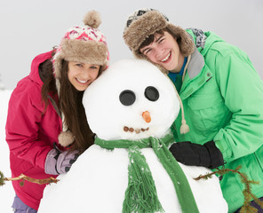 Two Teenagers Building Snowman On Ski Holiday In Mountains
