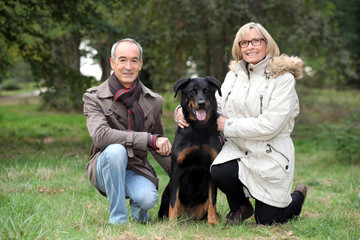 senior couple posing with their dog in a park