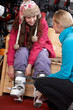 Sales Assistant Helping Teenage Girl To Try On Ski Boots In Hire