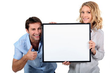 Couple holding a blank sign