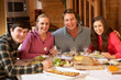 Teenage Family Enjoying Meal In Alpine Chalet Together