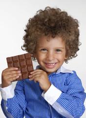 Niño sujetando una barra de chocolate,comiendo chocolate.