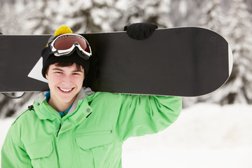 Teenage Boy With Snowboard On Ski Holiday In Mountains