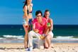 Mann und Frauen spielen Boule am Strand