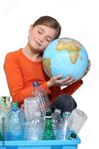 Little girl holding globe and recycling bottles