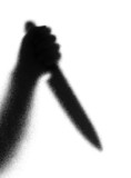 Knife in a hand. Silhouette. Photographed through the textured g