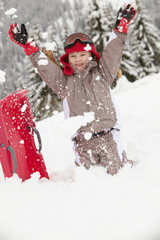 Young Girl Playing In Snow With Sledge On Ski Holiday In Mountai