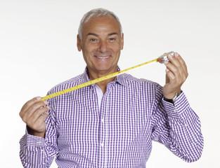 Señor sujetando una cinta métrica,metro y cálculo.