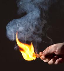 Burning match in hand. Smoke