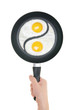 Fried eggs in the form of yin and yang on pan. Pan in hand on wh