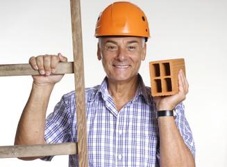 Señor  sujetando un ladrillo y una escalera,construcción.