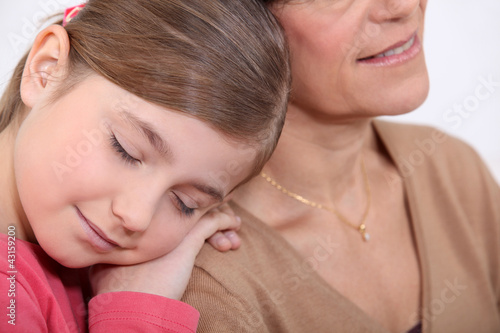 little girl resting on her grandmother's shoulder