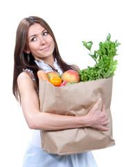 Woman holding a shopping bag full of fresh vegetables