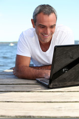 Man using his laptop on jetty
