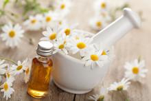 huile essentielle et des fleurs de camomille dans un mortier
