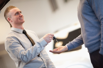 Smiling man giving keys to a man