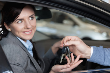 Smiling woman receiving keys from a man