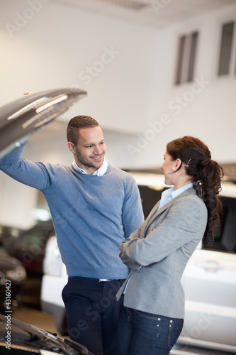 Smiling couple in front of an open car engine