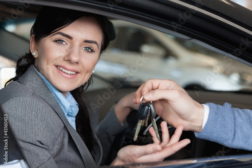 Smiling woman in a car receiving car keys