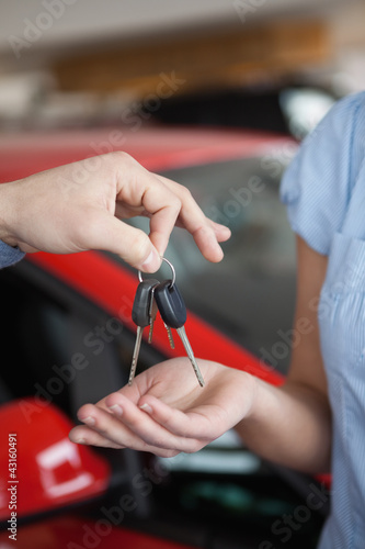 Car keys hold by someone over someone else hand
