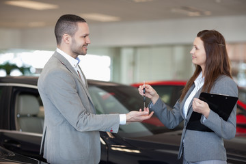 Woman giving car keys to a client