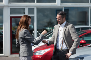 Businesswoman giving car keys to a man