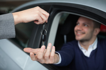 Man receiving car keys while sitting in his car
